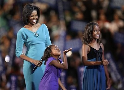 Watch the Special Video Biography of Michelle Obama Shown at the DNC Convention in August 2008. Photo: Sasha Obama at DNC in Denver blows a kiss to her dad on satellite TV.