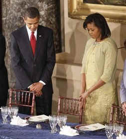President Barack Obama and First Lady Michelle Obama pray at the Inaugural Luncheon at Statuary Hall at the US Capitol. The first course of the Inauguration Luncheon is be served on replicas of Lincoln china selected by Lincoln's wife Mary Todd Lincoln.