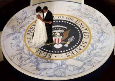First Lady Michelle Obama and President Barack Obama wow the cameras and attendees as they dance on the Presidential Seal at the Commander In Chiefs Inaugural Ball at the National Building Museum in Washington.