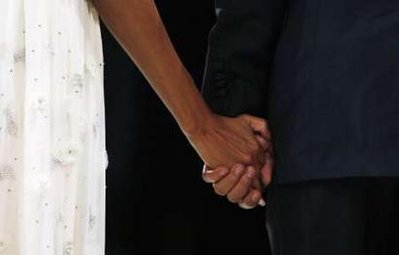 President Barack Obama and First Lady Michelle Obama hold hands at the Southern Regional Inaugural Ball at the National Guard Armory.