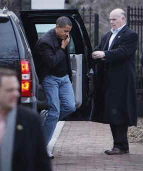 President Barack Obama arrives at a friend's house in Chicago while on his BlackBerry as he exits his motorcade SUV.