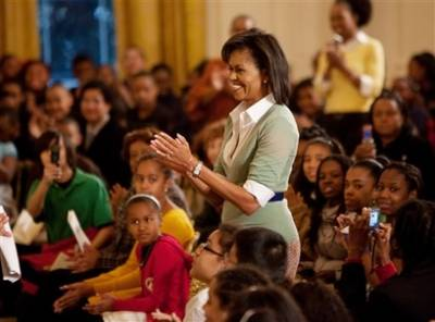 Michelle, Sasha, and Malia Obama watch the special performance of school children in the East Room of the White House. First Lady Michelle Obama spoke later to the students and pointed out a few historic White House facts.