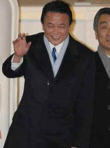 Japan's PM Taro Aso waves as he departs Tokyo for Andrews Air Force Base on February 23, 2009.