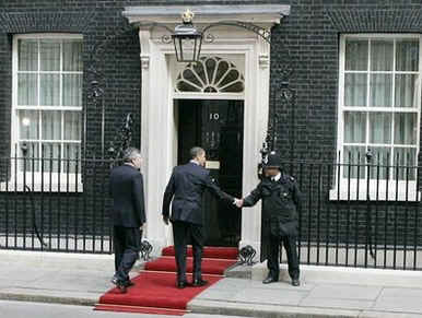President Obama shakes the hand of a London police officer as he returns to the Downing Street residence.