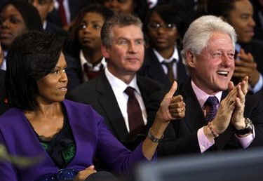 First Lady Micelle Obama sits next to Bill Clinton at the signing ceremony at the inner city Washington, DC school on April 21, 2009.