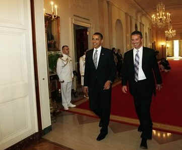 Gators Head Coach Urban Meyer walks into East Room with President Obama. Obama meets with the NCAA National Football Champion Florida Gators in the East Room of the White House.