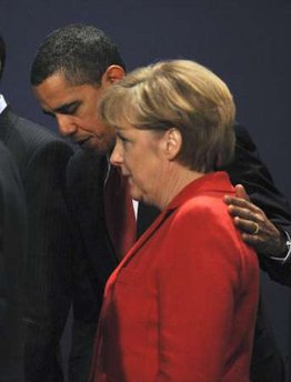 President Obama escorted German chancellor Angela Merkel from the stage after making gestures during the first G20 group photo.