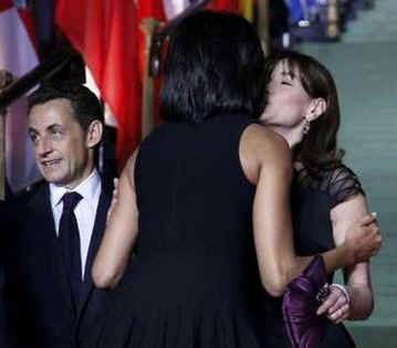 Michelle Obama embraces Carla Buni-Sarkozy at the Kurhaus in Baden-Baden, Germany.