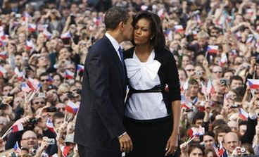 President Obama kisses Michelle before his public speech in the square of the old city capital surrounded by historic buildings.