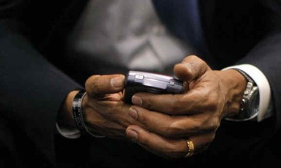 President Barack Obama with his Blackberry device between his hands.