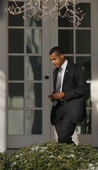 President Barack Obama uses his secure Blackberry then holsters the device on January 29, 2009 as he walks in the morning sun to the Oval Office.
