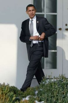 President Barack Obama holsters his Blackberry as he walks to the Oval Office on January 29, 2009.