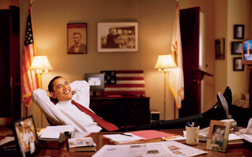 Senator Barack Obama relaxes in his Capitol Hill office in the fall of 2002. On the wall behind Barack Obama are photos of President Abraham Lincoln and Martin Luther King Jr.