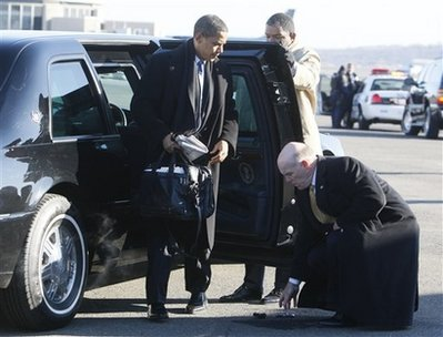 Barack Obama drops his Blackberry after getting out of his car at Reagan Airport in Washington. A Secret Service agent retrieves the device.