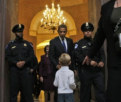 Barack Obama greets a 5 year old in a tour group after meeting with Speaker of the House Nancy Pelosi and other key Capitol Hill representatives in Washington, DC.