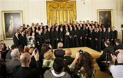 President Barack Obama presents the Commander In Chief Trophy to the Naval Academy Football Team in the East Room of the White House.
