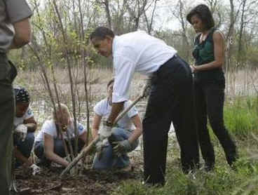 President Barack Obama and First Lady Michelle Obama plant trees with volunteers.