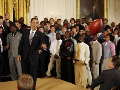 President Obama passes a football to his aide Reggie Love. President Barack Obama meets with the NCAA National Football Champion Florida Gators in the East Room of the White House.