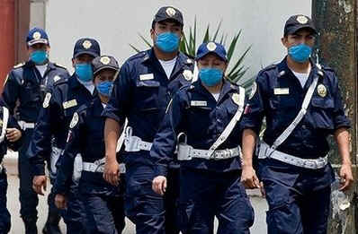 Mexican police wear protective masks in Mexico City on April 27, 2009.