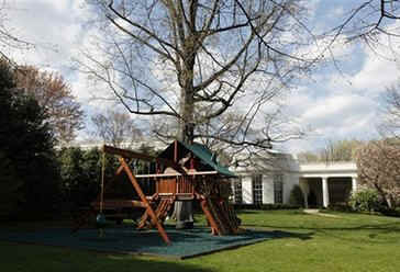 The Obama girls swing and play set with new padded mat made of recycled tires on the green grass of the White House Lawn.