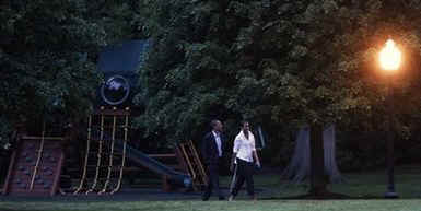 President Barack Obama and First Lady Michelle Obama return to the White House and walk across the South Lawn after a Saturday evening dinner.